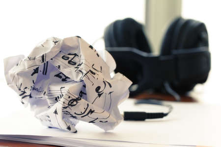 composing music concept with shallow DOF evenly matched jack of headphone and crumpled musical notes paper photo