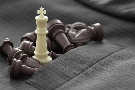 executive: close up of chess figure on suit background strategy or leadership concept
