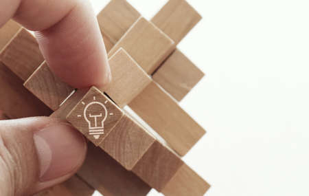 solve problem: close up of hand showing illuminated light bulb icon on a wooden block puzzle as innovation concept