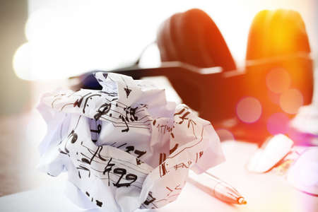 composing music concept with shallow DOF evenly matched crumpled musical notes paper and exposure bokeh photo
