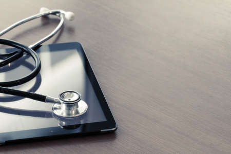 clinical: Studio macro of a stethoscope and digital tablet with shallow DOF evenly matched abstract on wood table background copy space