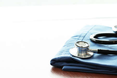 medical device: Stethoscope with blue doctor coat on wooden table with shallow DOF evenly matched and background