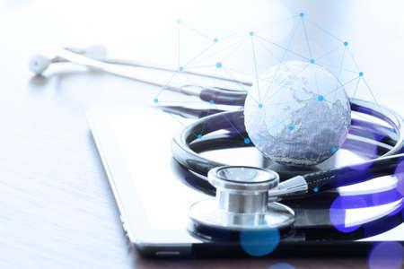 equipos medicos: Estudio macro de un estetoscopio y textura mundo con tableta digital con el DOF bajo igualados abstracto como el concepto de red m�dica Foto de archivo