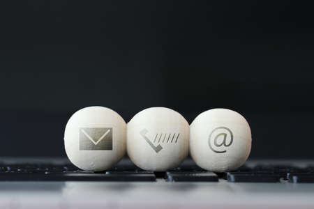 icon on wooden ball of website and internet contact us page concept on computer laptop  keyboard 스톡 콘텐츠