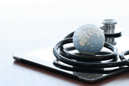 Studio macro of a stethoscope and texture globe with digital tablet with shallow DOF evenly matched abstract as medical network concept  photo