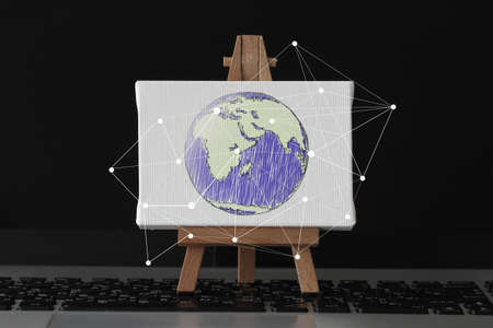 hand drawn globe with social network diagram on canvas and wooden easel on laptop computer as concept photo