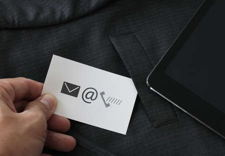 close up of businessman hand picking business card icon contact us concept from the pocket of gray suit jacket background