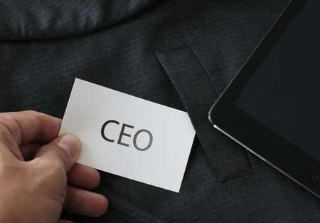 chief executive officers: close up of businessman hand picking business card reading CEO from the pocket of gray suit jacket background Stock Photo