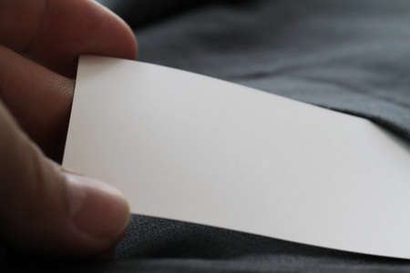 hand in pocket: close up of hand picking blank business card from gray suit pocket background