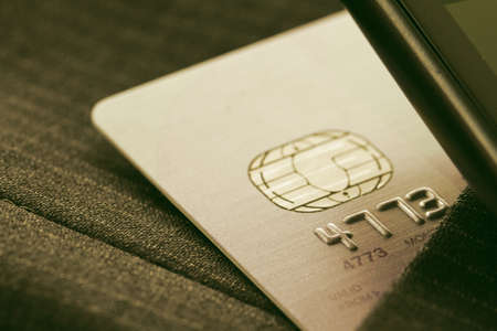 charge: Credit cards in very shallow focus with gray suit background