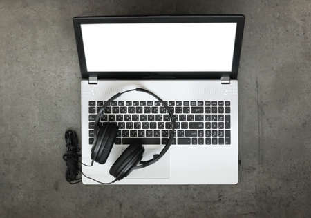 quavers: top view of workspace of composing music concept with headphone and blank screen computer laptop on texture desk background
