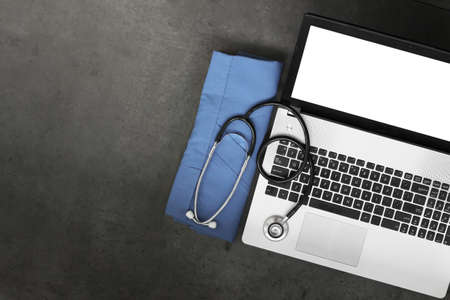 top view of workspace of medical with stethoscope and blue coat and blank screen computer laptop on texture desk background photo