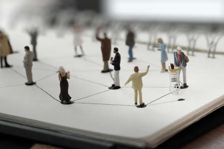 net book: close up of miniature people with social network diagram on open notebook on wooden desk as social media conept