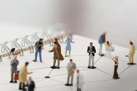 close-up van miniatuur mensen met een sociaal netwerk diagram op open notebook op houten bureau als social media conept Stockfoto