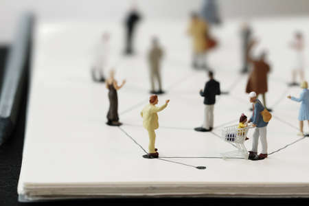 conept: close up of miniature people with social network diagram on open notebook on wooden desk as social media conept
