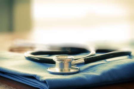 doctor: Estetoscopio con el escudo azul médico en mesa de madera con el DOF bajo igualado y fondo