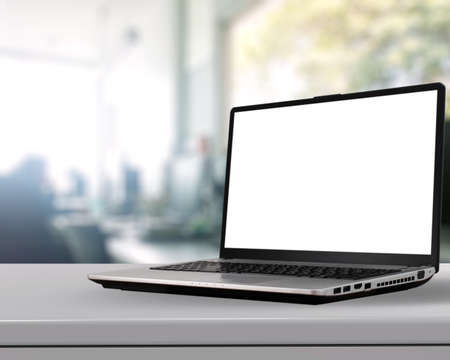Laptop with blank screen on white desk with blurred background as concept
