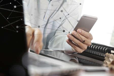 Mano dell'uomo d'affari con laptop schermo vuoto e telefono cellulare con diagramma di social network in ufficio