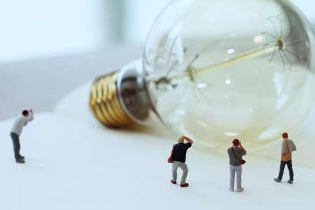 Creative idea concept - miniature photographer with vintage light bulb on open paper notebook Stockfoto