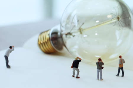 Creative idea concept - miniature photographer with vintage light bulb on open paper notebook Stock Photo