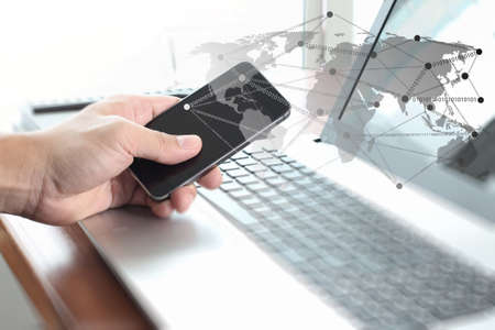 Businessman hand using laptop and mobile phone with social network diagram on wooden desk as concept photo