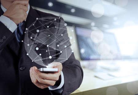 tecnología informatica: Mano de empresario con teléfono móvil con el diagrama de red social en el escritorio de madera como concepto
