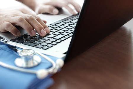オフィスでラップトップ コンピューターを使用して医師の手のクローズ アップ