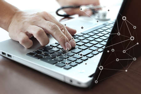 close up of Doctor hand using laptop computer with medical network media diagram as concept photo