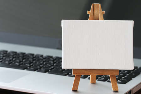 blank canvas: blank canvas and wooden easel on laptop computer as concept