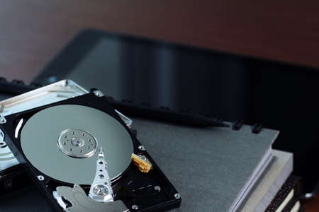 diskdrive: Close up of open computer hard disk drive on desk and notebook Stock Photo