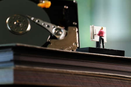 drafting table: Big data concept-miniature engineer working wirh drafting table with open harddisk background