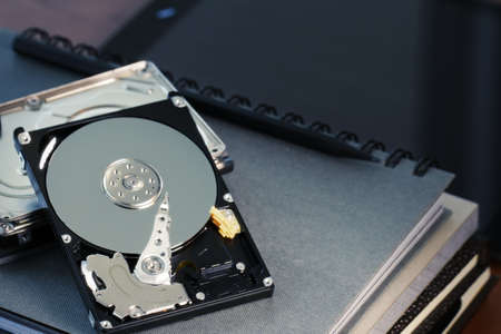 megabyte: Close up of open computer hard disk drive on desk and notebook Stock Photo