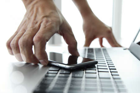 Businessman hand using laptop and mobile phone in office photo