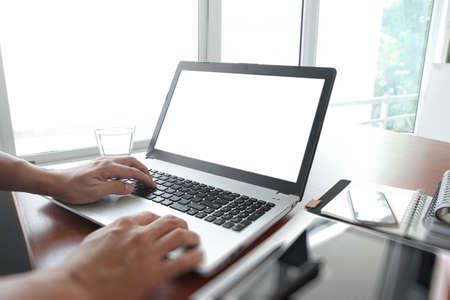 typing: Cierre para arriba del hombre de negocios mano trabajando en equipo port�til pantalla en blanco en el escritorio de madera como concepto
