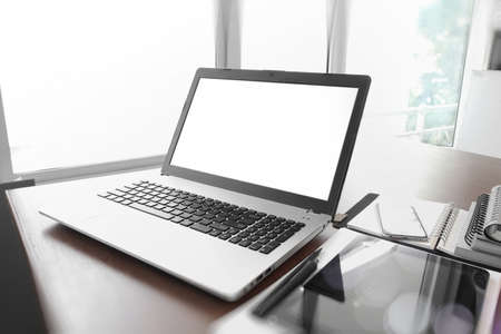 Office workplace with  blank screen  laptop and smartphone on wood table photo