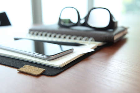 Office workplace with laptop and smartphone and stylus on wood table photo