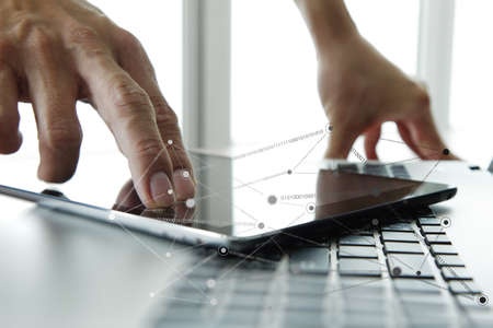 technology transaction: Businessman hand using laptop and mobile phone with social network diagram on wooden desk as concept