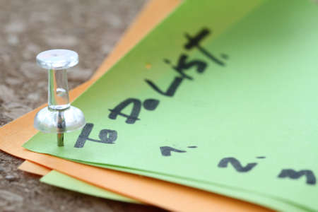 to do list: close up of pin and to do list word on sticky note with cork board as concept Stock Photo
