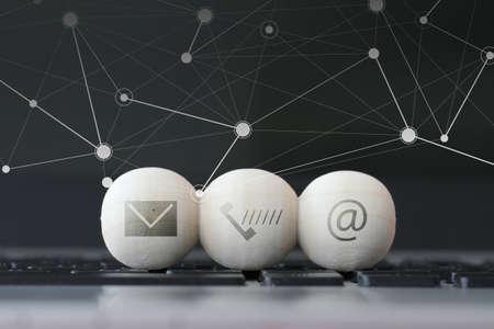 comunicar: icono en bola de madera de la página web y de Internet contacto página concepto en el teclado de la computadora portátil y el diagrama de los medios sociales