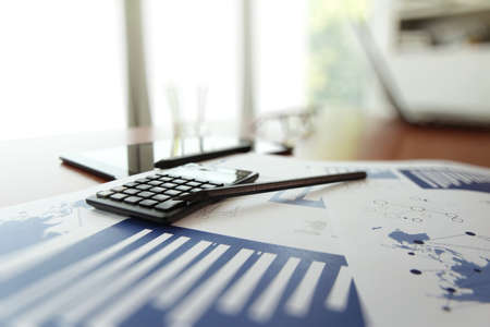 business documents on office table with calculator and digital tablet as work space business concept photo