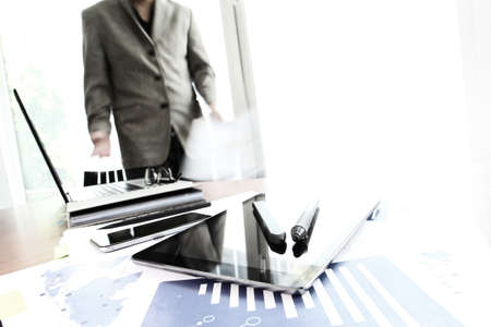 business documents on office table with smart phone and digital tablet and graph business diagram and man working in the background photo