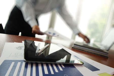 business documents on office table with smart phone and digital tablet and man working in the background photo