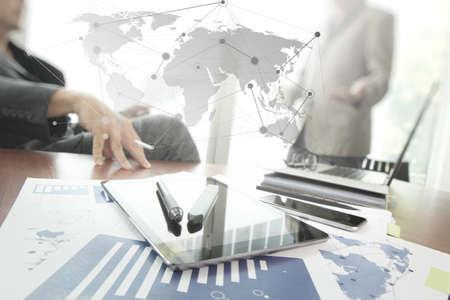 tecnolog�a informatica: documentos de negocios en la mesa de oficina con tel�fono inteligente y la tableta digital y l�piz y dos colegas en discusiones datos en segundo plano