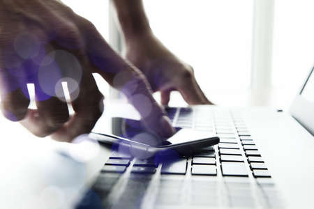 Businessman hand using laptop and mobile phone  on wooden desk as concept photo