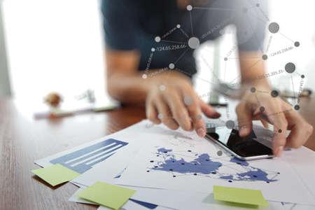 revisando documentos: documentos de negocios en la mesa de oficina con teléfono inteligente y tableta digital y el hombre que trabajan en segundo plano Foto de archivo
