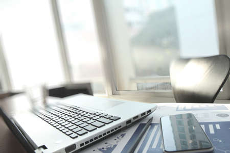 unrecognized: business documents on office table with laptop computer and smart phone as work space business concept