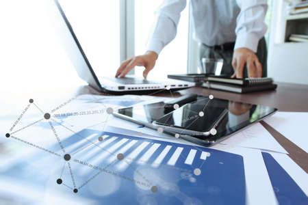 finance: business documents on office table with digital tablet and man working with smart laptop computer background with social network diagram concept