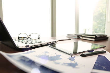 documentos de negocios en la mesa de la oficina con el ordenador portátil y la tableta digital como espacio de trabajo concepto de negocio