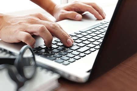 mecanografía: Cierre para arriba del hombre de negocios mano trabajando en equipo portátil pantalla en blanco en el escritorio de madera como concepto