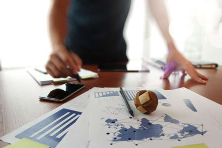 creative: Moving Image of Business creative designer working wooden texture globe with smart phone on business document in office desk as internet concept
